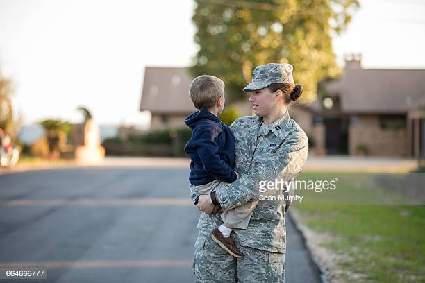 Female soldier carrying son at military air force base