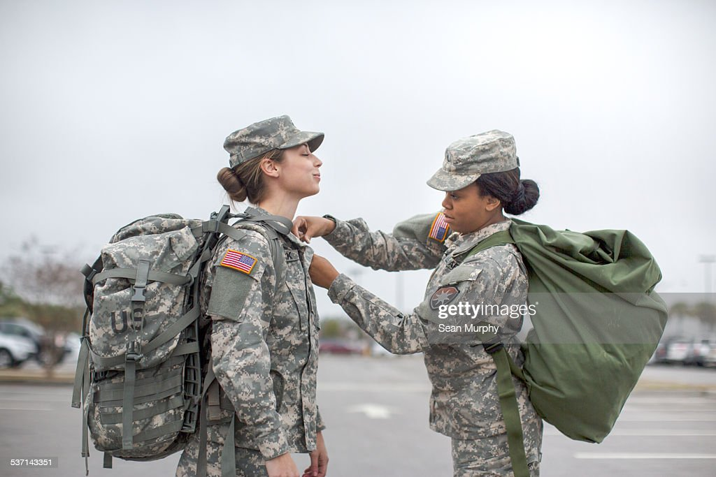 Female Soldier Helping Another Soldier with Shirt : Stock Photo
