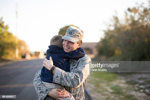Female soldier hugging son at air force military base