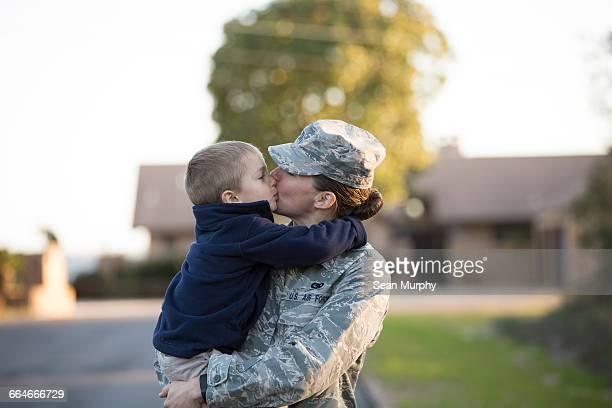 Female soldier kissing son at military air force base