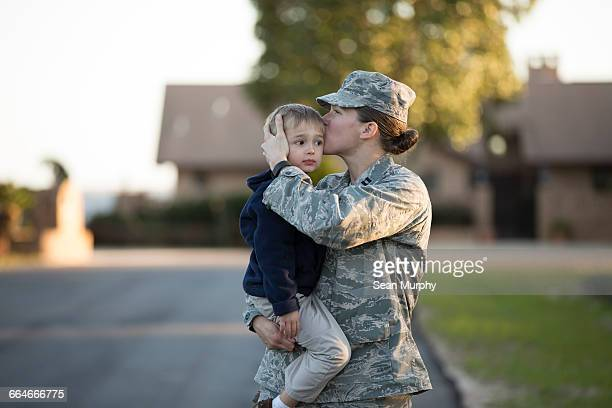 Female soldier kissing son on forehead at military air force base