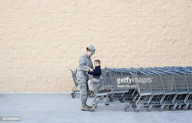 Female soldier lifting son into supermarket trolley at air force military base