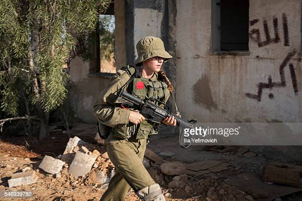A female soldier patorls as Israeli male and female combat soldiers of the Bardales battalion take part in a long day of practise in a heavy fog on...