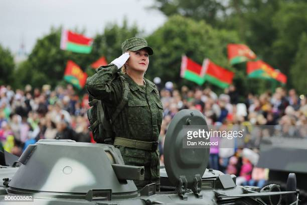 A female soldier salutes as tanks roll past Belarusian President Alexander Lukashenko during the Independence Day Parade on July 3 2017 in Minsk...