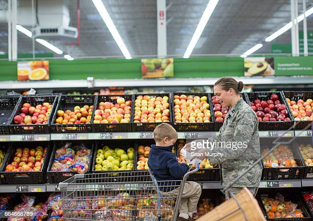 Female soldier shopping with son in supermarket at air force military base