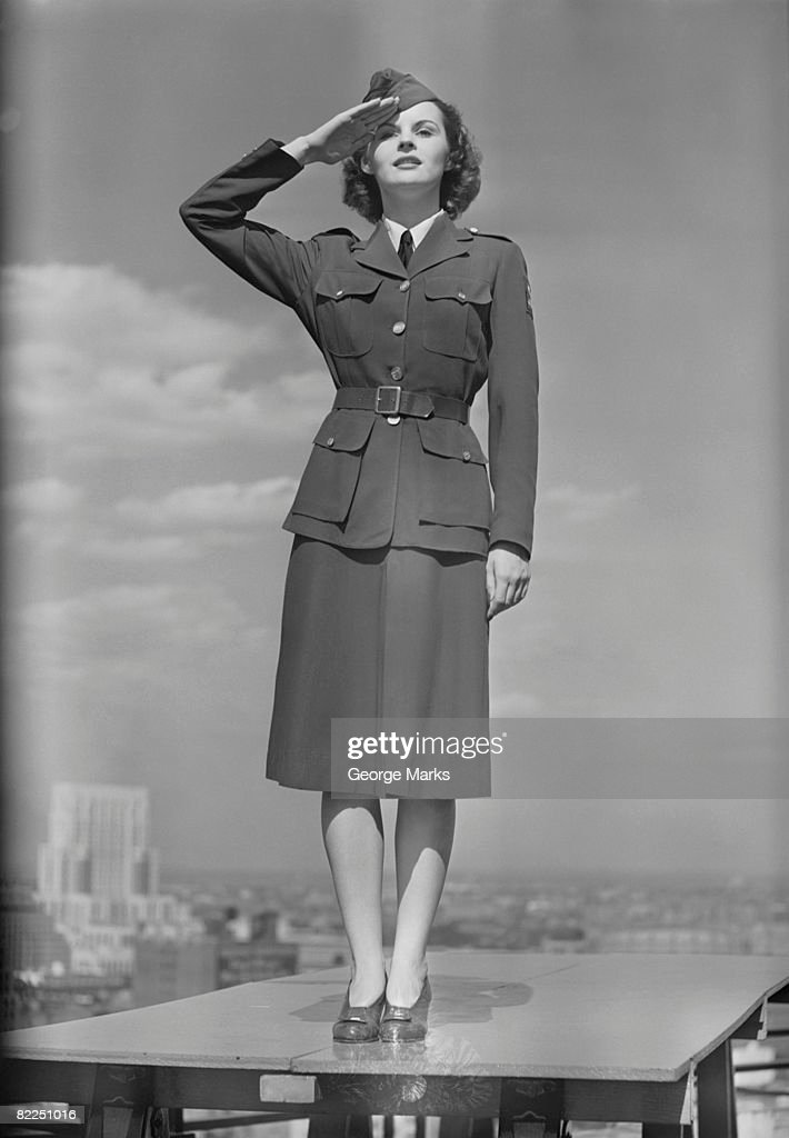Female soldier standing on table and saluting : Stock Photo