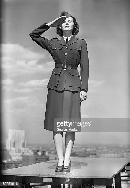 Female soldier standing on table and saluting