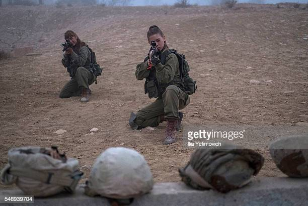 A female soldier takes aim as Israeli male and female combat soldiers of the Bardales battalion take part in a long day of practise in a heavy fog on...