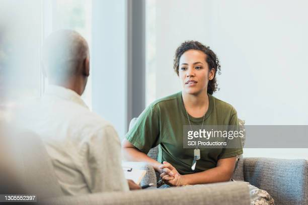female soldier talking with mental health professional - post traumatic stress disorder stock pictures, royalty-free photos & images
