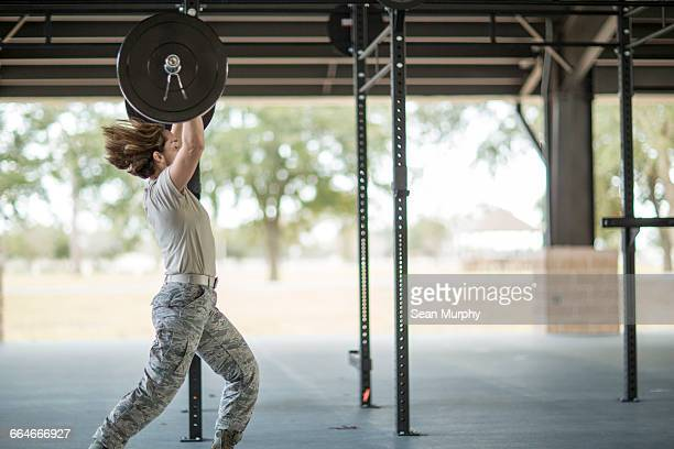 Female soldier weight lifting barbell at military air force base