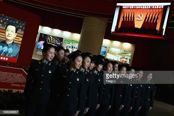 Female soldiers pose for photos in front of the portrait of China's President Hu Jintao as visiting an exhibition entitled 'Scientific Development...