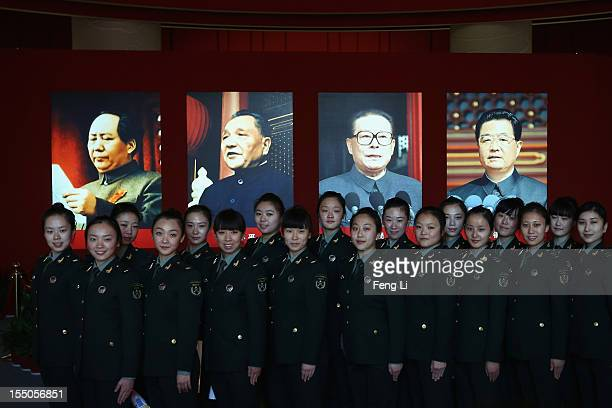 Female soldiers pose for photos in front of the portraits of China's President Hu Jintao and former President Jiang Zemin as visiting an exhibition...