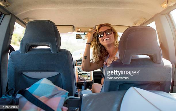 Female solo backpacker traveller smiling in car