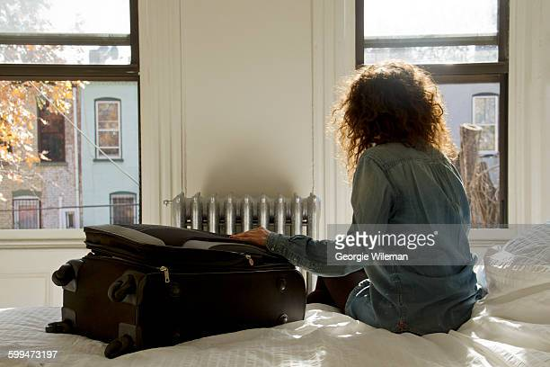 Female Solo Traveller Sat On Bed In AirBnB
