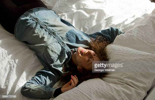 Female Solo Traveller Smiling On Bed In AirBnB