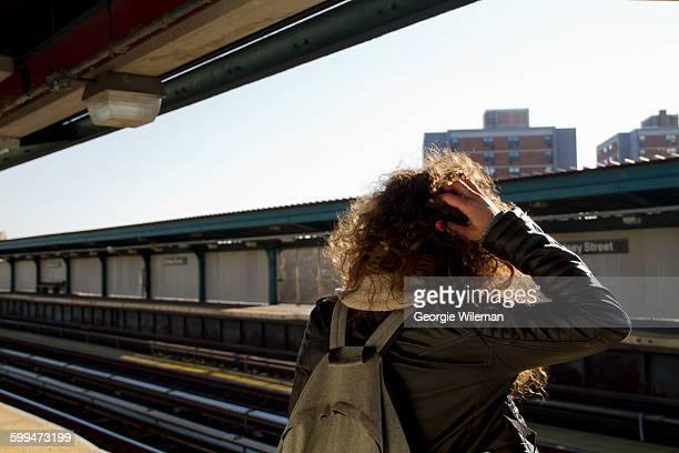 Female Solo Traveller Stood On Train Platform