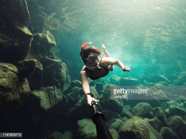 female solo traveller taking a selfie while she is snorkelling at las grietas, galapagos islands. - nomadic people stock pictures, royalty-free photos & images
