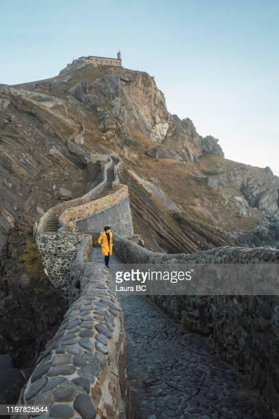 female solo traveller walking at san juan de gaztelugatxe from far away - ビスカヤ県 ストックフォトと画像