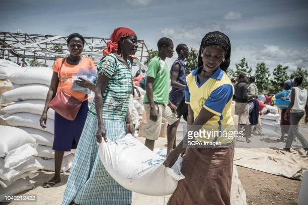 Female South Sudanese refugees seen carrying a bag of 50KG food supply from the distribution point at Bidi Bidi refugee settlement