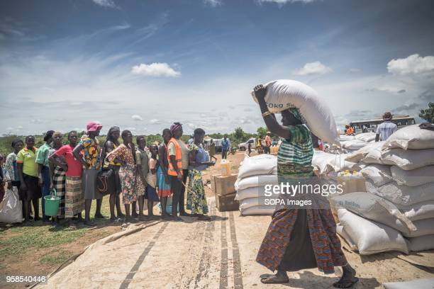 A female South Sudanese refugees seen carrying a pack of 50 KG of cassava flour on top of the her head while others line up to get their food...