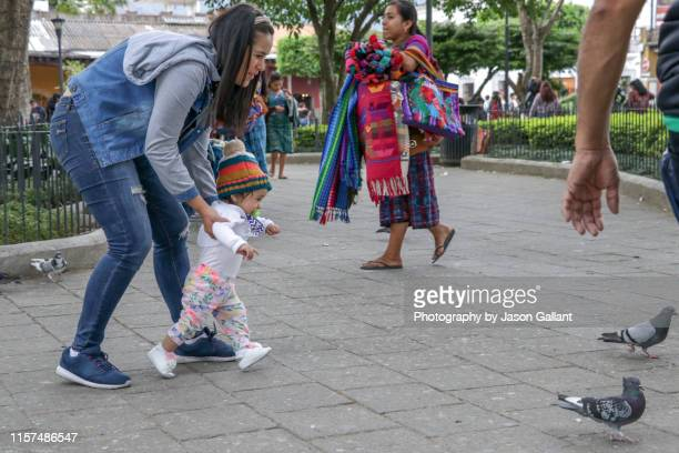 female souvenir vendor walking beside mother with baby in the plaza central park in antigua, guatemala - guatemala city stock pictures, royalty-free photos & images