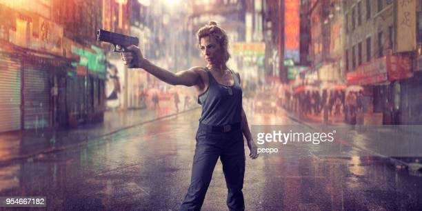 female special forces action hero soldier with gun in chinatown - hero stock photos and pictures