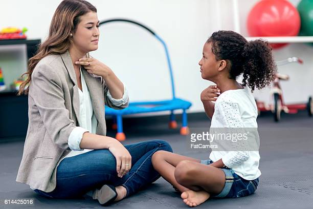 Female speech therapist assisting young African American girl