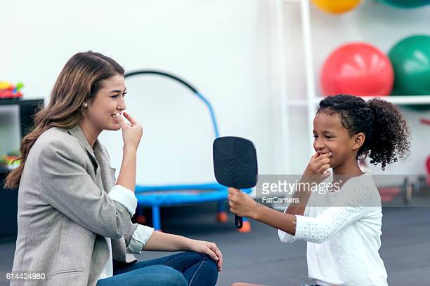 Female speech therapist helping an African American girl in therapy