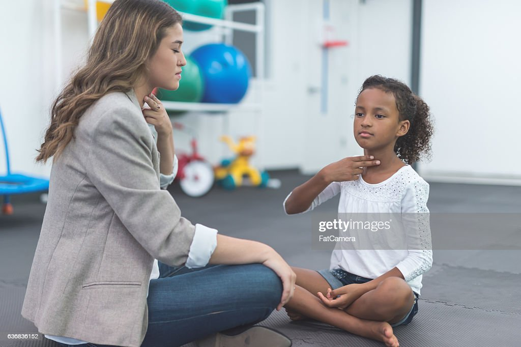 A female speech therapist working with an ethnic child : Stock Photo