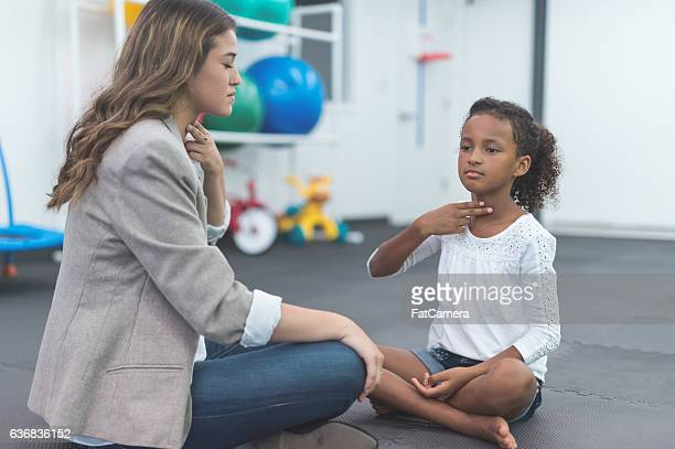 A female speech therapist working with an ethnic child