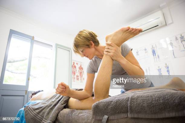 female sports massage therapist hard at work - massage stock photos and pictures