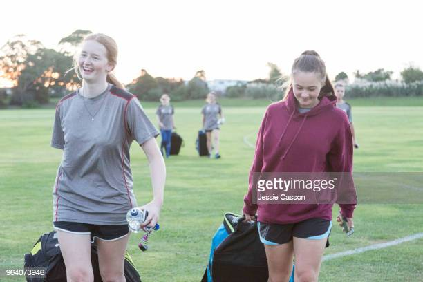 female sports team players walk onto/off pitch with their sports gear bags - play off stock pictures, royalty-free photos & images
