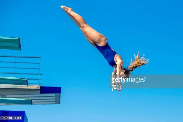 female springboard diver jump - diving into water stock photos and pictures