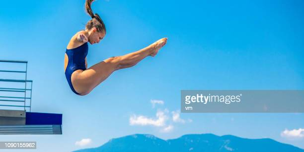 female springboard diver jump - diving sport stock pictures, royalty-free photos & images