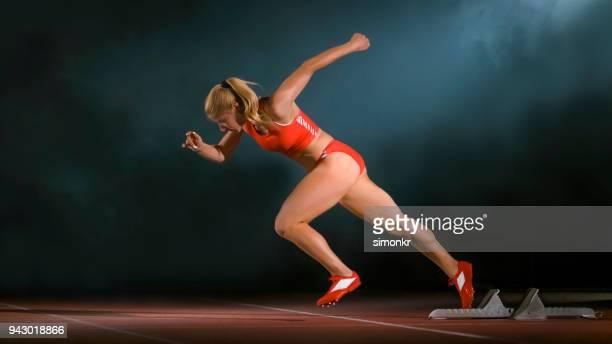 スターティング ブロックを残して女性スプリンター - スプリント競技 ストックフォトと画像