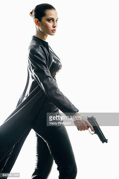 Female spy with gun walking against white background