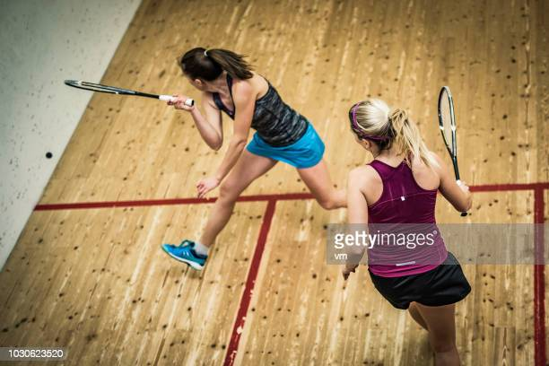 female squash player hitting the ball - squash sport stock pictures, royalty-free photos & images