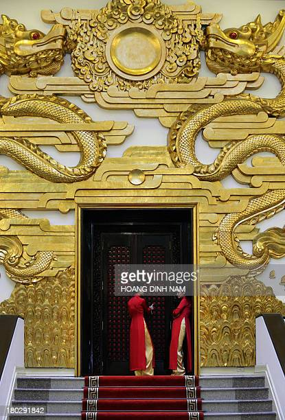 Female staff in traditional 'Ao Dai' dress stand outside the entrance of a meeting room as visiting Singaporean Prime Minister Lee Hsien Loong and...