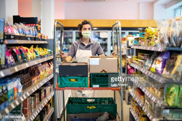 female staff working in grocery store re-stocking goods - assistant stock pictures, royalty-free photos & images