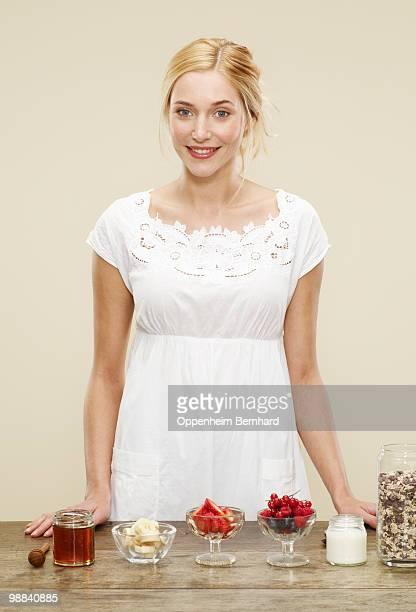 female standing in front of breakfast ingredients