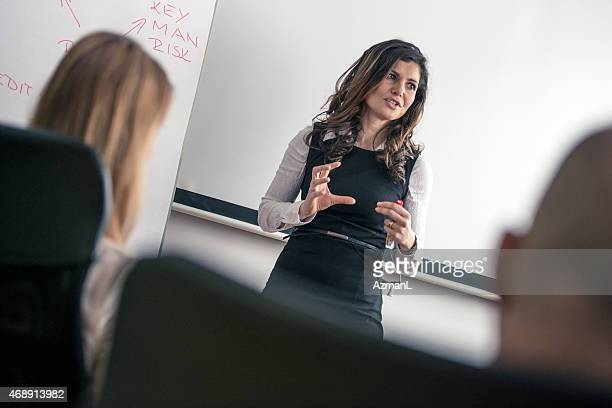 Female standing in front of people doing business training