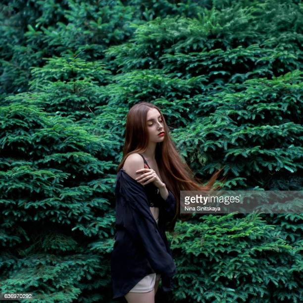 female standing near the wall of fir tree branches, surreal - donne mentre si spogliano foto e immagini stock