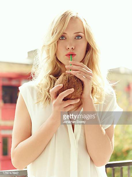 Female standing on balcony drinking out of coconut