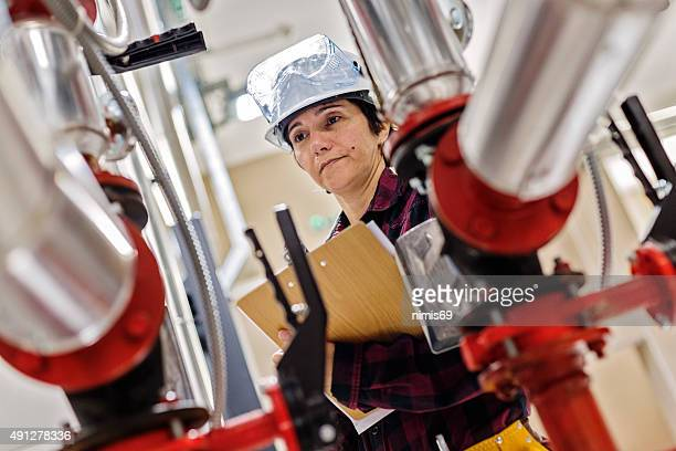 female stationary engeneer at work - air valve stock photos and pictures