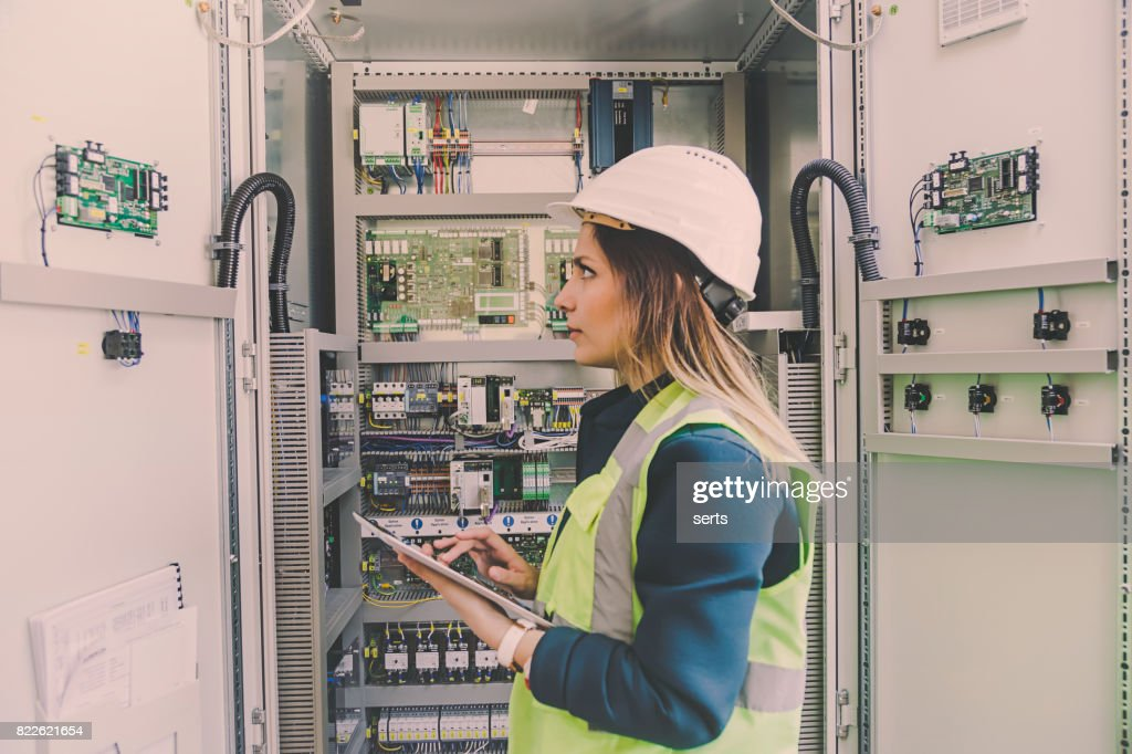 Female stationary engineer take notes at energy control room : Stock Photo