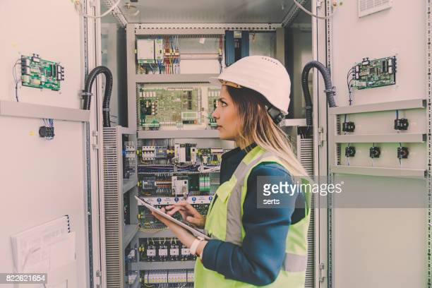 female stationary engineer take notes at energy control room - fuse stock photos and pictures