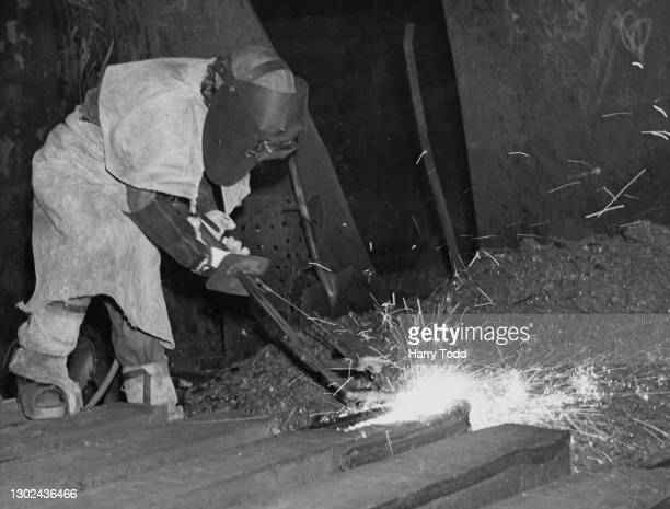 Female steel foundry worker in full protective clothing uses an oxy ferraline torch to weld on 30th January 1943 at the Park Gate Iron and Steel...