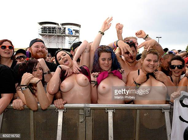 Image contains nudity MELBOURNE AUSTRALIA FEBRUARY 22 Female Steel Panther fans in the front row of the audience lift their tshirts and show their...