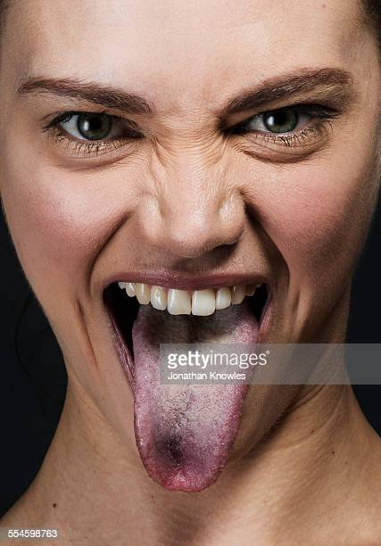 female sticking out her tongue - human tongue stock pictures, royalty-free photos & images