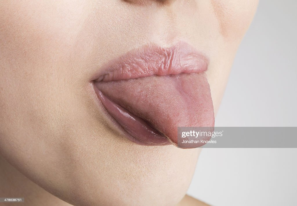 Female sticking out tongue, close up : Stock Photo